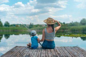 Två personer sitter på en brygga och fiskar